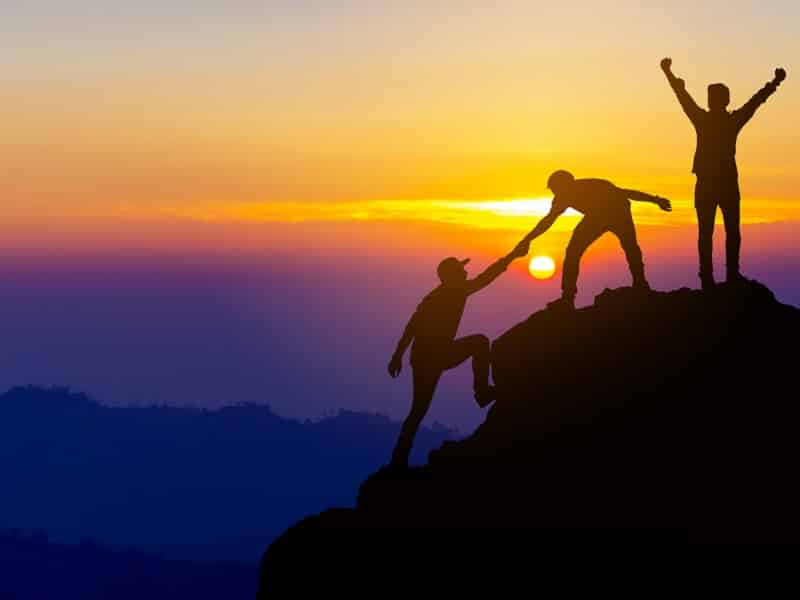 people helping each other up mountain