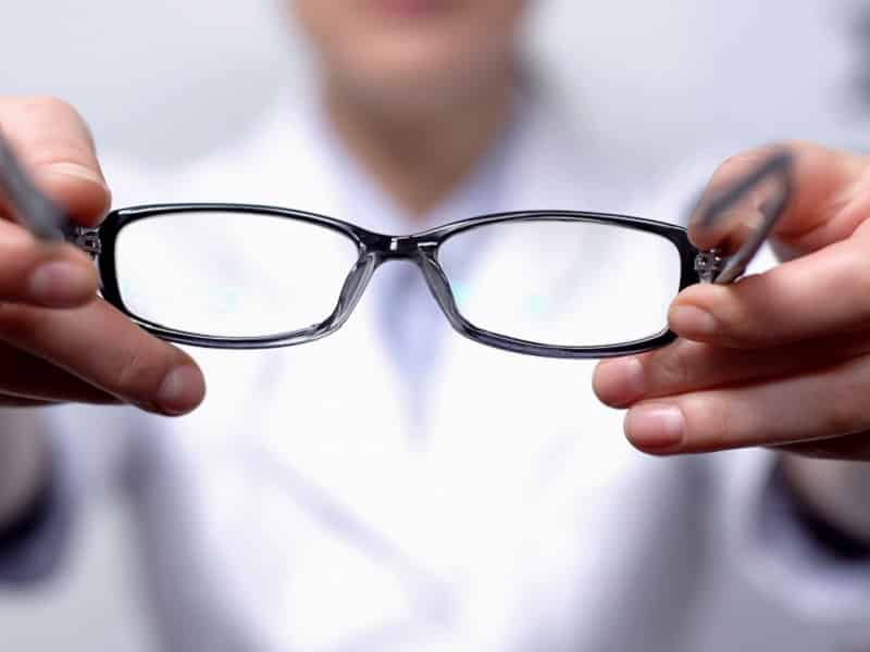 glasses being held out to viewer