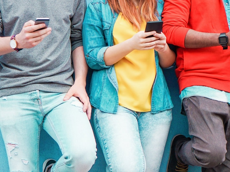 group youths on smartphones