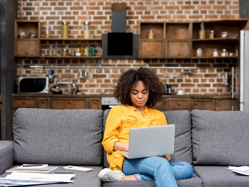woman on sofa working on laptop